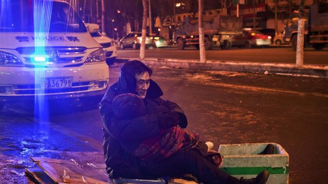 A man, whose surname is He, cuddles the body of his dead wife during a sub-zero evening in Shenyang