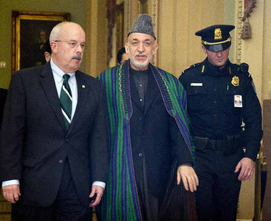 Afghanistan President Hamid Karzai, is escorted by Sergeant of Arms of the Senate Terrance Gainer, left, as he walks to a meeting with U.S. sanators on Capitol Hill in Washington, Wednesday, Jan. 9, 2013.    (AP Photo/Manuel Balce Ceneta)