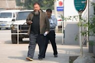 Chinese artist Ai Weiwei (C) leaves court in Beijing on September 27, 2012. Chinese authorities will shut down the company founded by Ai, his lawyer said Tuesday, in the latest step in what the dissident artist has called a campaign of persecution to silence his activism