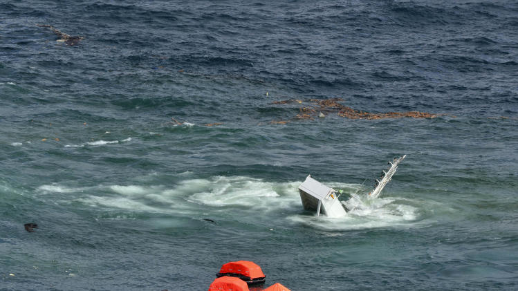 In this photo provided by Maritime New Zealand, half of the cargo ship Rena is nearly totally submerged on a reef near Tauranga, New Zealand, Tuesday, Jan. 10, 2012. The 774-foot (236-meter) vessel split in two over the weekend amid heavy seas and now the stern section is slipping from the Astrolabe reef and sinking. (AP Photo/Maritime New Zealand) EDITORIAL USE ONLY