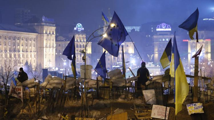 Ukrainian pro-EU demonstrators stand guard on a barricade during a rally at Independence Square in central Kiev