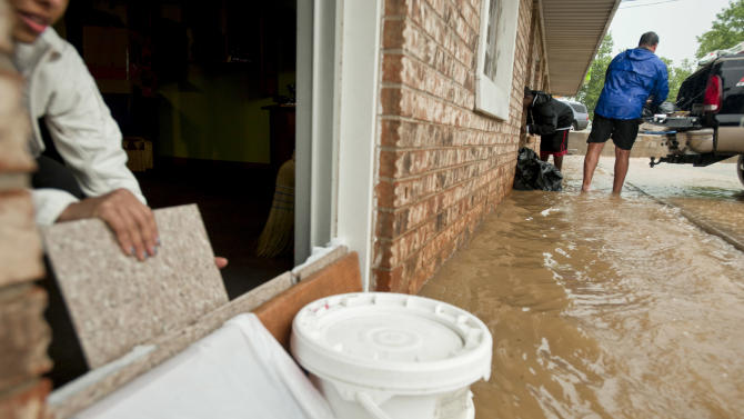 Business owners work to prevent rising waters from entering their business along College Ave. on Monday, April 25, 2011, in Fayetteville, Ark. Much of Northwest Arkansas was hit with heavy rain and flash floods. (AP Photo/Beth Hall)