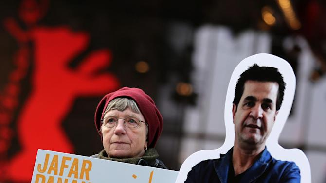 """A protester shows a banner next to a portrait of Iranian director Jafar Panahi prior to the screening of the movie 'Closed Curtain' during the 63rd annual Berlin International Film Festival in Berlin, Germany, Tuesday Feb.12. 2013. The  movie from the  dissident Iranian director that defies a ban on filmmaking and reflects his frustration at being unable to work officially is making its debut at the Berlin film festival. """"Closed Curtain"""" is co-directed by Jafar Panahi and fellow Iranian filmmaker and his longtime friend Kamboziya Partovi. Panahi, who has won awards at several major film festivals in the past, was sentenced to house arrest and a 20-year ban on filmmaking in 2011 after being convicted of """"making propaganda"""" against Iran's ruling system.  Partovi presented the movie Tuesday at the Berlin festival, where it's one of 19 films competing for the top Golden Bear award. It's filmed entirely inside a seaside villa, much of the time with curtains drawn, and the two directors are the lead actors. (AP Photo/dpa, Kay Nietfeld)"""