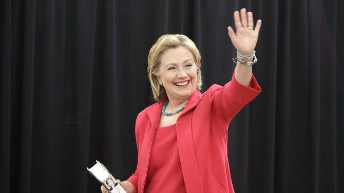 """Former Secretary of State Hillary Clinton waves as she arrives at a Little Rock, Ark., Wal-Mart store for a book signing event Friday, June 27, 2014. She carries a copy of her book """"Hard Choices"""".(AP Photo/Danny Johnston)"""
