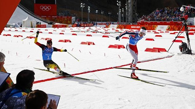 Norway's Joergen Graabak (R) crosses the finish line as second-placed Germany's Fabian Riessle (L), falls, at the end of the Nordic Combined team Gundersen event of the Sochi 2014 Winter Olympic Games, at the RusSki Gorki Ski Jumping Center