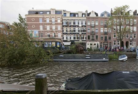 A tree lies fallen on a houseboat, sinking it, in a canal along the Jacob van Lennepkade street in Amsterdam