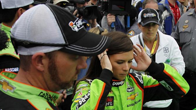 Danica Patrick, center, prepares to get in her car before the start of the NASCAR Daytona 500 Sprint Cup Series auto race at Daytona International Speedway, Sunday, Feb. 24, 2013, in Daytona Beach, Fla. (AP Photo/Terry Renna)