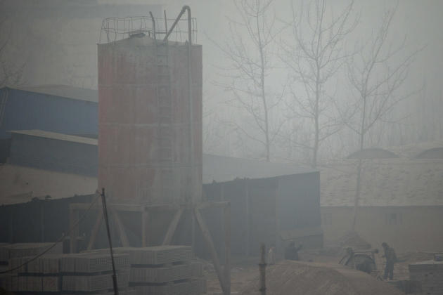 In this photo taken on Wednesday, Feb. 26, 2014, men work in a cement plant on a severely polluted day in Shijiazhuang, in northern China's Hebei province. Combatting pollution has shot up the age