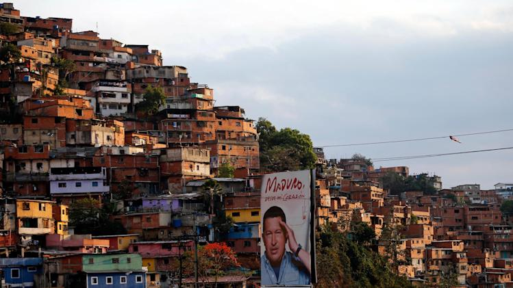 In this March 27, 2014 photo, a poster of Venezuela's late President Hugo Chavez stands in the Petare shanty town of Caracas, Venezuela. Many in Petare, a sprawling hillside slum of crumbling brick buildings on the eastern outskirts of Caracas, have come to rely on Cuban physicians for free health services in a country where private care is too expensive for the poor and public hospitals have a dismal reputation. (AP Photo/Fernando Llano)