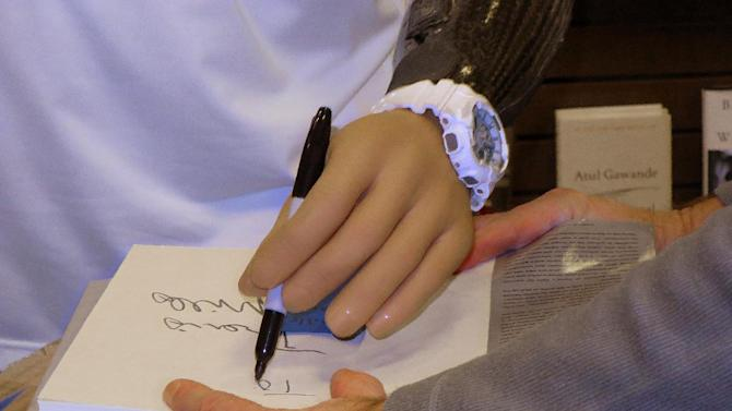 """Using his prosthetic arm, retired Army Staff Sgt. Travis Mills signs a book at an event promoting his book, """"Tough As They Come,"""" on Tuesday, Dec. 1, 2015, in Augusta, Maine.  Mills, who lives in Manchester, Maine, lost all four limbs as a result of an IED blast in 2012 in Afghanistan. (AP Photo/David Sharp)"""