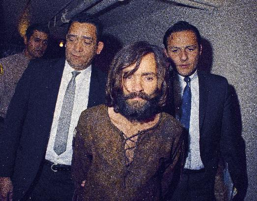 """FILE  This 1969 file photo shows Charles Manson being escorted to his arraignment on conspiracy-murder charges in connection with the Sharon Tate murder case  Los Angeles, Calif. Mass murderer Anders Behring Breivik's shocking testimony to a Norwegian court has revived a debate about how much of a public platform mass-murderers should be given in trials. Such atrocities are often waged for attention and carried out in the name of political or religious goals, and a trial gives perpetrators more of what they crave: a huge audience.  Cult leader Charles Manson, who persuaded others to kill for him, refused to testify in the raucous 1970 trial of him and other members of his """"Manson Family."""" In an unusual proceeding, Manson was allowed to testify outside the jury's presence so that the judge could rule on whether his testimony was admissible in front of jurors.(AP Photo)"""