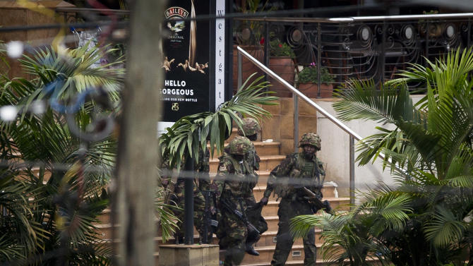 Soldiers from the Kenya Defense Forces carry a wounded colleague, following the sound of explosions and gunfire, out of the Westgate Mall in Nairobi, Kenya Sunday, Sept. 22, 2013. Associated Press journalists at the scene of a hostage standoff said a barrage of gunfire erupted from the upscale Kenyan mall Sunday morning and moments later two wounded Kenyan security forces were carried out of the mall. (AP Photo/Ben Curtis)