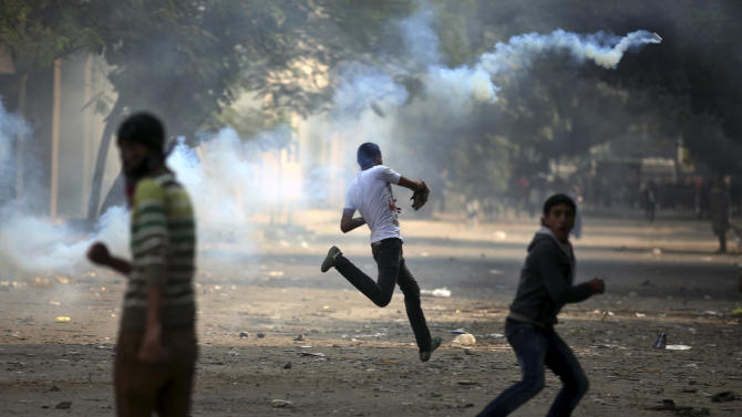 An Egyptian protester runs to throw a tear gas canister fired from security forces during clashes near Tahrir square, where an opposition rally has been called for to voice rejection of President Morsi's seizure of near absolute powers, in Cairo, Egypt, Tuesday, Nov. 27, 2012. Egyptian protesters and police clashed in Cairo on Tuesday just hours ahead of a planned massive rally by opponents of the country's Islamist president demanding he rescinds decrees that granted him near-absolute powers.(AP Photo/ Khalil Hamra)