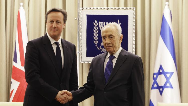 Israel's President Peres and British Prime Minister Cameron shake hands during their meeting in Jerusalem