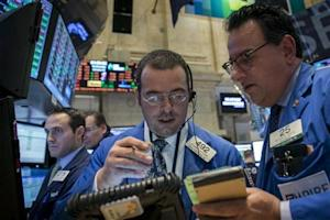 Traders Richard Scardino and Peter Costa discuss a trade on the floor of the New York Stock Exchange