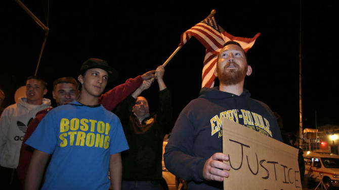 "Garrett Plath, right, holds a sign and Toni Zagami, left, wears a ""Boston Strong"" shirt as they stand outside the Dyer-Lake Funeral Home in North Attleborough, Mass, where a vehicle believed to be carrying the body of Boston Marathon bombing suspect Tamerlan Tsarnaev arrived, Thursday, May 2, 2013. About fifteen people from the area stood outside the funeral home in protest. (AP Photo/Charles Krupa)"