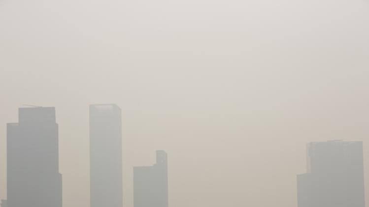 A woman wearing a mask walks on a bridge during a hazy day in downtown Shanghai