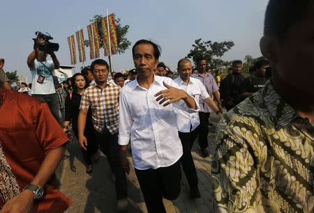 "Indonesian presidential candidate Joko ""Jokowi"" Widodo walks while waiting for the results announcement by the Elections Commission, at Waduk Pluit in Jakarta"
