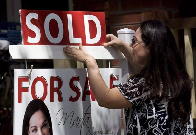 "A real estate agent puts up a ""sold"" sign in front of a house in Toronto on April 20, 2010. THE CANADIAN PRESS/Darren Calabrese"