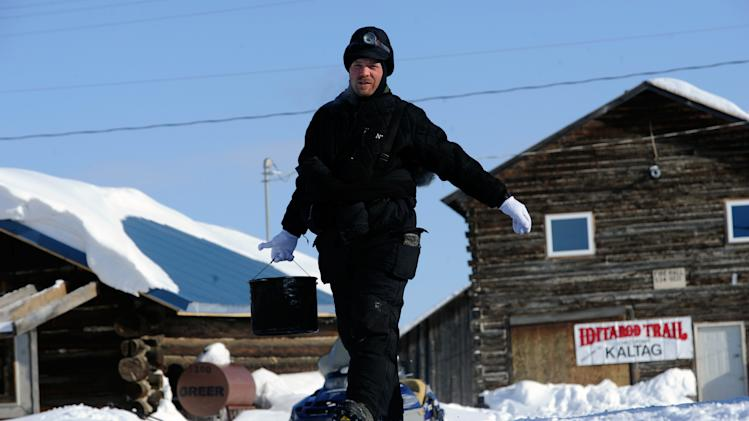 Aaron Burmeister carries a pot of water at the Kaltag checkpoint of the Iditarod Trail Sled Dog Race on Saturday, March 10, 2012, in Kaltag, Alaska. (AP Photo/The Anchorage Daily News, Marc Lester)