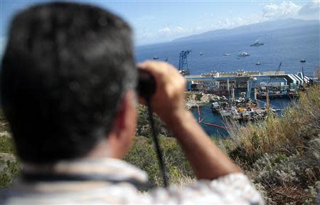 A person looks on with binoculars as the capsized cruise liner Costa Concordia lies on its side next to Giglio Island