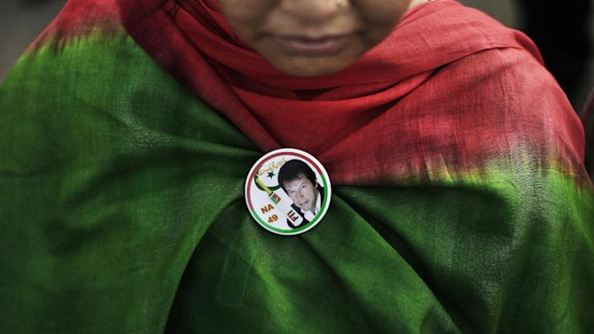 A Pakistani supporter of former cricket star-turned-politician, and leader of Pakistan Tehreek-e-Insaf party, Imran Khan, wearing a pin bearing Khan's image, takes part during a rally in Islamabad, Pakistan, Thursday, May 9, 2013. Pakistan is scheduled to hold parliamentary elections on May 11, the first transition between democratically elected governments in a country that has experienced three military coups and constant political instability since its creation in 1947. The parliament's ability to complete its five-year term has been hailed as a significant achievement. (AP Photo/Muhammed Muheisen)