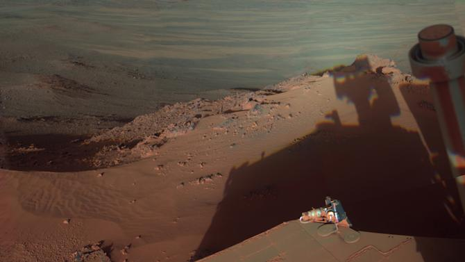 In this undated image provided by NASA, Mars Rover Opportunity catches its own late-afternoon shadow in a view eastward across Endeavour Crater on Mars. The rover used a panoramic camera between about 4:30 and 5:00 p.m. local Mars time to record images taken through different filters and combined into this mosaic view. Most of the component images were recorded during the 2,888th Martian day, or sol, of Opportunity's work on Mars, which corresponds to March 9, 2012 on Earth. The view is presented in false color to make some differences between materials easier to see, such as the dark sandy ripples and dunes on the crater's distant floor. Opportunity has been studying the western rim of Endeavour Crater since arriving there in August 2011. (AP Photo/NASA/JPL-Caltech/Cornell/Arizona State University)