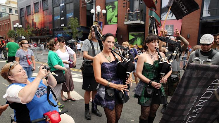 "Bagpipers and models dressed as Highlanders promoting the STARZ original series ""Outlander"" are seen during San Diego Comic-Con on Friday, July 25, 2014 in San Diego. ""Outlander"" premieres on STARZ August 9, 2014. (Photo by Matt Sayles/Invision for STARZ/AP Images)"
