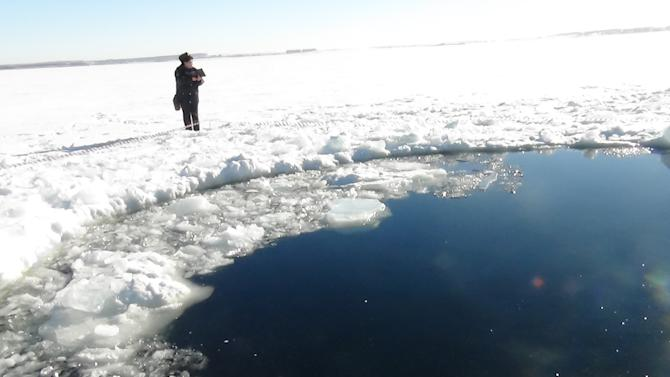 A circular hole in the ice of Chebarkul Lake where a meteor reportedly struck the lake near Chelyabinsk, about 1500 kilometers (930 miles) east of Moscow,  Russia,  Friday, Feb. 15, 2013. A  meteor streaked across the sky and exploded over Russia's Ural Mountains with the power of an atomic bomb Friday, its sonic blasts shattering countless windows and injuring nearly 1,000 people. (AP Photo)