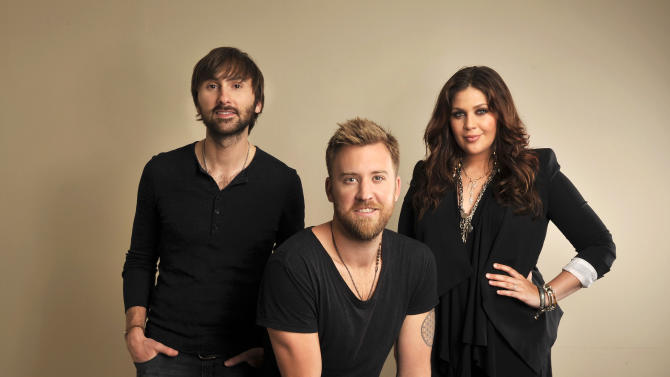 """This March 22, 2013 photo shows members of Lady Antebellum, from left, Dave Haywood, Charles Kelley and Hillary Scott in Nashville, Tenn., to promote their latest album, """"Golden."""" (Photo by Donn Jones/Invision/AP)"""