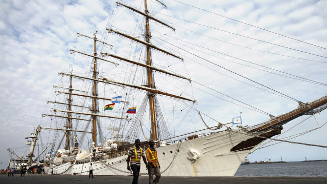 Port workers walk past the three-masted ARA Libertad, a symbol of Argentina's navy, as it lies docked at the port in Tema, outside Accra, Ghana, Tuesday, Oct. 23, 2012. Argentina has hired an Air France charter to fly nearly 300 navy cadets home from Ghana after failing to persuade the government there to reverse the seizure of its tall ship. Argentina said Monday that 281 crew members from Argentina and a half-dozen other countries will fly to Buenos Aires on Wednesday, leaving the captain with a skeleton crew to maintain the ship at port in Ghana.(AP Photo/Gabriela Barnuevo)