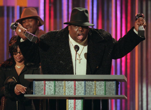 "** FILE ** In this Dec. 6, 1995 file photo, Notorious B.I.G., who won rap artist and rap single of the year, clutches his awards at the podium during the annual Billboard Music Awards in New York. The children of late rapper Notorious B.I.G. will star in an animated series about maintaining the hip-hop legend's Brooklyn recording studio. Ossian Media announced Monday, March 11, 2013, that ""House of Wallace"" will feature 16-year-old C.J. and 19-year-old T'yanna Wallace. (AP Photo/Mark Lennihan, File)"