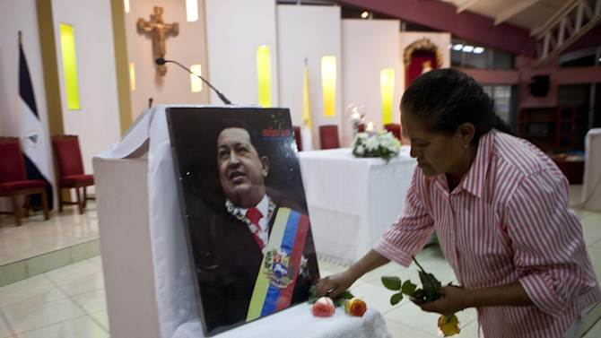 """A woman places flowers in front of an image of Venezuela's President Hugo Chavez in preparation for a mass in support of him in Managua, Nicaragua, Wednesday Dec. 12, 2012. Venezuela's Information Minister Ernesto Villegas expressed hope about the Chavez's returning home for his Jan. 10 swearing-in for a new six-year term after his cancer surgery in Cuba, but said in a written message on a government website that if Chavez doesn't make it, """"our people should be prepared to understand it."""" (AP Photo/Esteban Felix)"""