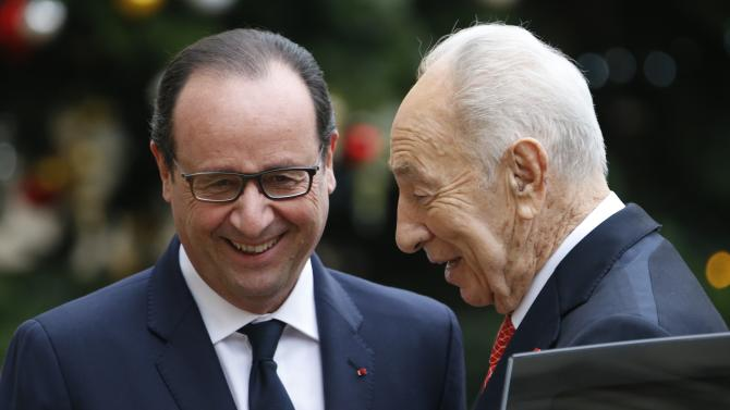 French President Francois Hollande welcomes former Israel's President Shimon Peres as he arrives for a meeting at the Elysee Palace in Paris