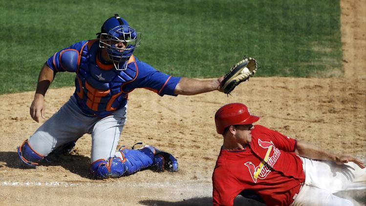 New York Mets catcher Anthony Recker, left, tags out St. Louis Cardinals' Stephen Piscotty as he slides into home plate off a fly ball by teammate Scott Moore in the eighth inning of an exhibition spring training baseball game, Sunday, March 16, 2014, in Jupiter, Fla