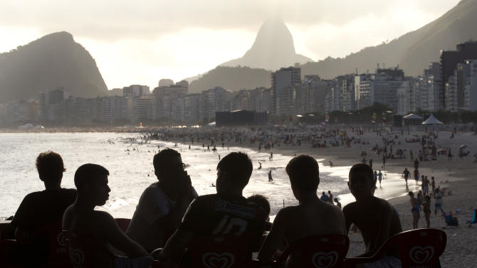 Men are silhouetted against Copacabana beach in Rio de Janeiro, Brazil, Thursday, Dec. 26, 2013. Sports fans on a budget may want to bypass the World Cup and wait until the 2016 Olympics before making a trip to Brazil, especially considering estimated hotel rates in Rio de Janeiro during both events. Tourists visiting the city for the 2014 World Cup could end up paying three times more for hotels compared to those coming for the Olympics two years later, according to recent industry studies and research by The Associated Press. (AP Photo/Silvia Izquierdo)