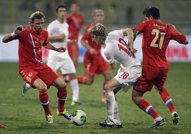 Serbia's Dusan Basta, second right, fights for the ball with Russia's Dimitri Tarasov, left, during a friendly match Dubai, United Arab Emirates, Friday Nov. 15, 2013