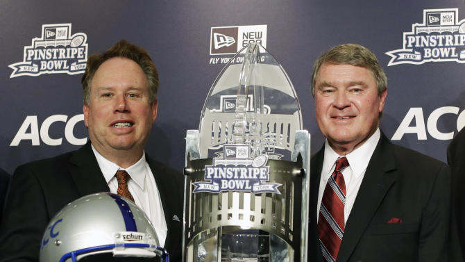 Pinstripe Bowl executive director Mark Holtzman, left, and Atlantic Coast Conference Commissioner John Swofford pose for photos during a news conference to announce the New York Yankees and the college football Pinstripe Bowl have reached a multi-year partnership with the ACC at Yankee Stadium, Tuesday, June 25, 2013, in New York. (AP Photo/Kathy Willens)