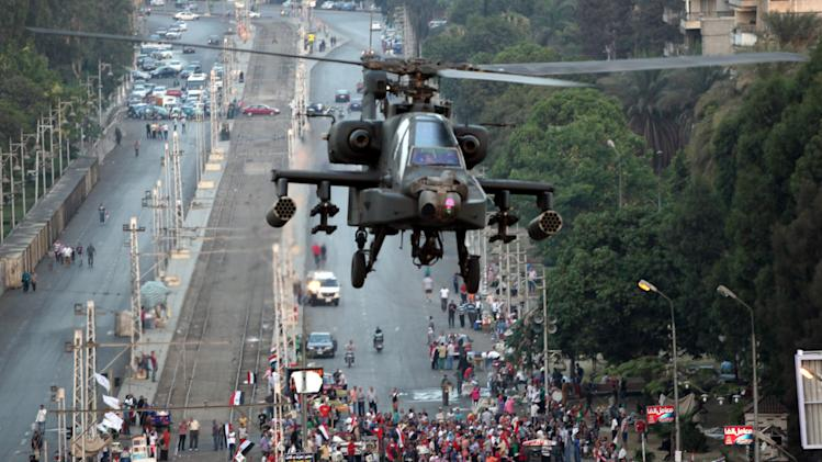 "A military attack helicopter flies near the presidential palace in Cairo, Egypt, Friday, July 5, 2013. The top leader of Egypt's Muslim Brotherhood has vowed to restore ousted President Mohammed Morsi to office, saying Egyptians will not accept ""military rule"" for another day. General Guide Mohammed Badie, a revered figure among the Brotherhood's followers, spoke Friday before a crowd of tens of thousands of Morsi supporters in Cairo. A military helicopter circled low overhead. (AP Photo/Khalil Hamra)"