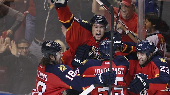 As fans, background, react, Florida Panthers' players Shawn Matthias (18), Ed Jovanovski (55) and Tyson Strachan (23) help Scottie Upshall (19) celebrate his goal during the third period of Game 5 in a first-round NHL Stanley Cup playoff hockey series against the New Jersey Devils in Sunrise, Fla., Saturday, April 21, 2012. The Panthers won 3-0.  (AP Photo/J Pat Carter)