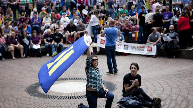 FILE - Community members and local leaders hold a rally in Terry Schrunk Plaza in Portland, Ore. on June 26, 2013 to celebrate the Supreme Court's rulings on the same-sex marriage. Activists and Democratic politicians in several states hope to repeal the bans in their states - in Oregon, Ohio and Arkansas with a possible ballot measure in 2014, in Nevada and Michigan with referendums in 2016. (AP Photo/The Oregonian, Allison Milligan)