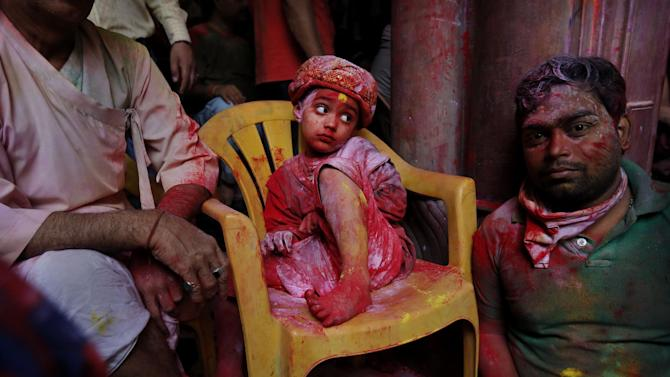 A young Hindu devotee sits covered in colored dye at the Banke Bihari temple, dedicated to Lord Krishna, during Holi festival celebrations in Vrindavan, India, Tuesday, March 26, 2013. Holi, the festival of colors celebrates the arrival of spring. (AP Photo/Kevin Frayer)