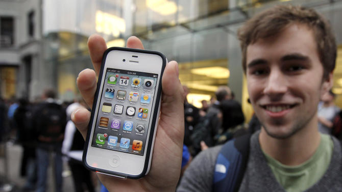 Elliott Johns, of Boston, displays an iPhone 4S in front of an Apple Store location in Boston, Friday, Oct. 14, 2011. The faster iPhone with better software and an improved camera went on sale in seven countries Friday as hundreds of buyers camped out for hours to be among the first to get one. (AP Photo/Steven Senne)