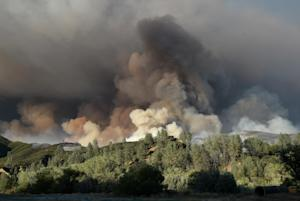 A plume of smoke rises above a hillside as the Rocky…