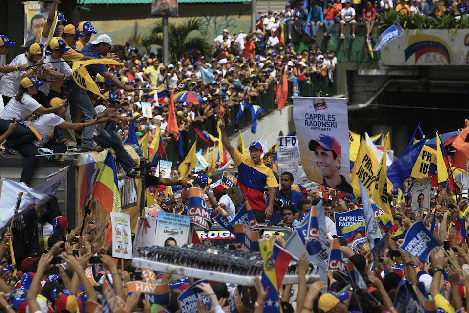 CORRECTS BYLINE - Opposition presidential candidate Henrique Capriles, center, gestures to supporters during a campaign rally in Caracas, Venezuela, Sunday, Sept. 30, 2012. Presidential elections in Venezuela are scheduled for Oct. 7. (AP Photo/Fernando LLano)