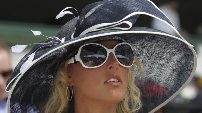 Stephanie Harris, from Lexington, Ky., waits for the start of a race in the grandstand before the 138th Kentucky Derby horse race at Churchill Downs, Saturday, May 5, 2012, in Louisville, Ky. The Run for the Roses draws them to Churchill Downs. But what race goers wear is as much a spectacle in itself. (AP Photo/Michael Conroy)