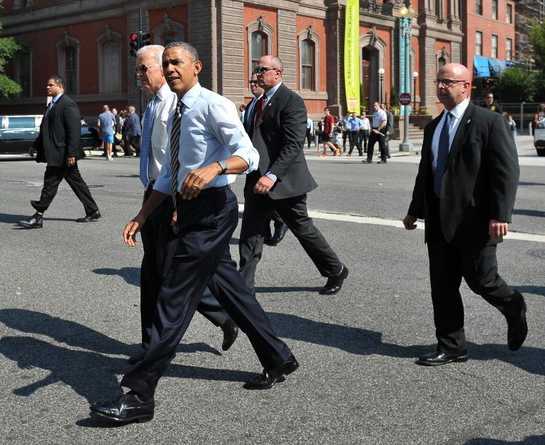 US President Barack Obama and US Vice President Joe Biden walk across 17th Avenue to get lunch at a nearby deli in Washington, DC on October 4, 2013
