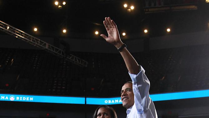President Barack Obama and first lady Michelle Obama wave to the crowd after speaking during a campaign rally at The Ohio State University, Saturday, May 5, 2012 in Columbus, Ohio . (AP Photo/Haraz N. Ghanbari)