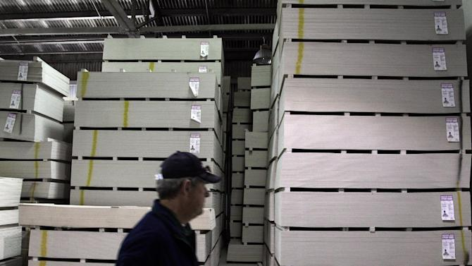 In this Thursday, April 19, 2012, file photo, a man walks past a stack of drywall that was manufactured in 2008, at the closed National Gypsum drywall factory in Lorain, Ohio. Demand for U.S. factory goods fell again in April as orders in a key sector that tracks business investment fell for a second straight month.  (AP Photo/Jae C. Hong)