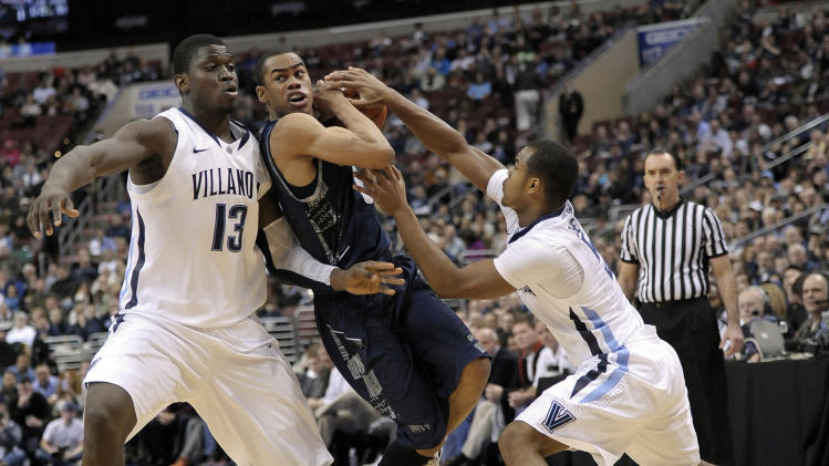 Georgetown's Markel Starks, middle, drives between Villanova's Tony Chennault, right, and Mouphtaou Yarou, left, during the first half of an NCAA college basketball game, Wednesday, March 6, 2013, in Philadelphia. (AP Photo/Michael Perez)